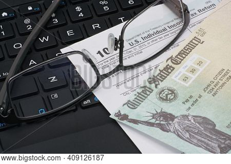 Us Irs Internal Revenue Service Income Tax Filing Form 1040 With Eyeglasses On Keyboard.