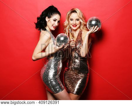 Party and celebration concept: Two glamour women, girlfriends in luxury glitter sequins dress and bright visage holding disco balls and glass of wine, dance over red background