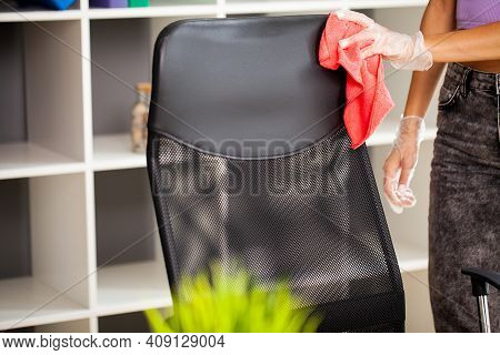 Woman Cleaning Office Chair With A Wipe