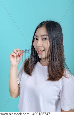 Smiling Asian Woman Holding Orthodontic Retainer On Blue Screen Background. Dental Care And Healthy