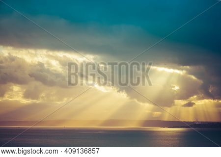 A Dramatic Sunset Through The Clouds Over The Ocean With Rays Of Light Piercing The Clouds.
