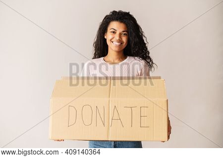 Kind Smiling African American Female Volunteer With Curly Dark Hair Holding A Cardboard Box, Donatin