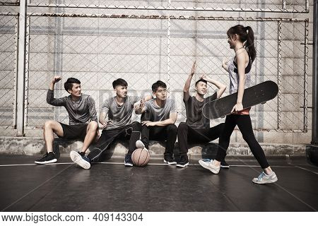Young Asian Adult Woman Skateboarder Giving A Group Of Young Men Hi-five
