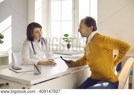 Middle Aged Patient Seeing Professional Doctor And Telling Her About His Backache