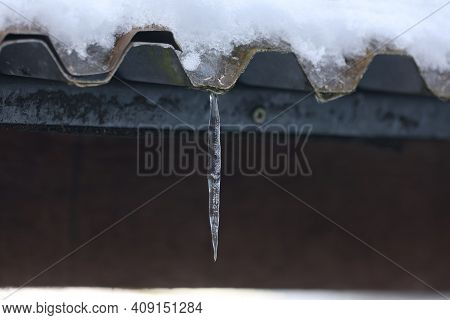 The Snow On The Roof Melts And Forms Ice Icicles.
