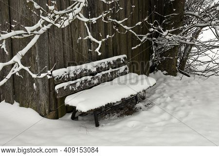 Old Wooden Bench In Winter Covered With Snow