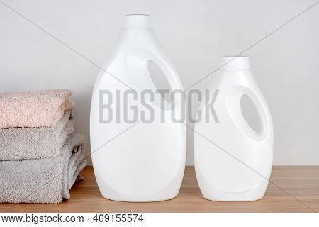 Bottles Of Detergent And Fabric Softener With Clean Towels On Wooden Table. Containers Of Cleaning P