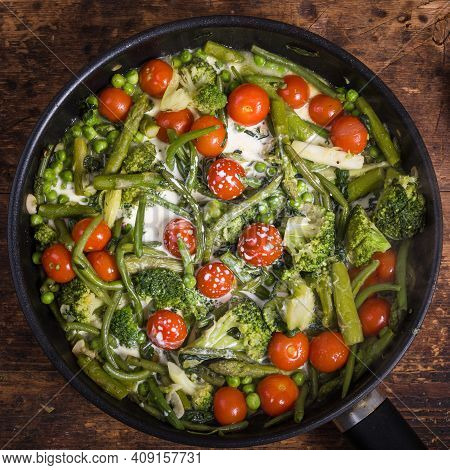 Cooking A Healthy Vegetable Dish In A Frying Pan - Broccoli, Asparagus, Peas And Beans With Cherry T