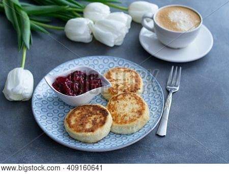Syrniki, Curd Or Cottage Cheese Pancakes With Cherry Jam And Coffee On A Grey Background With White