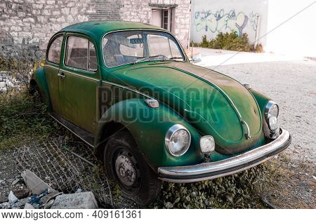 Trikala, Greece - February 6, 2021: A Dirty Old Abandoned Green-coloured Classic Volkswagen Beetle W