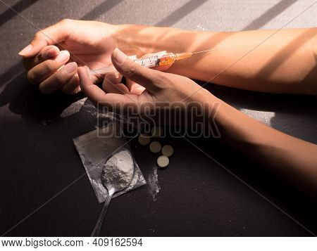 Hard Drugs With Hand Asian Women Injecting Heroin Into A Vein On Dark Wooden Black Background. Narco