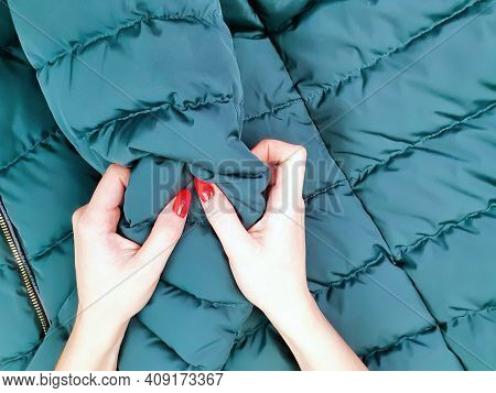 Young Woman Testing Green Puffer Jacket Textile. Female Hands With Red Manicure And Green Down Jacke