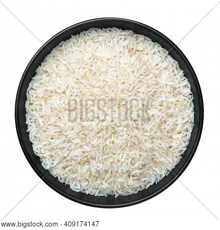 Raw Long Grain Rice In Black Ceramic Bowl Isolated On White. Heap Of Uncooked Basmati Or Jasmine Ric