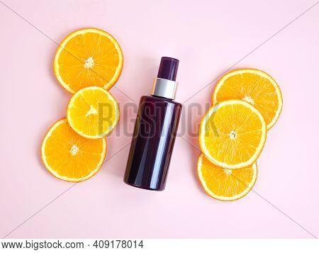 Mockup Of Unbranded Brown Plastic Spray Bottle And Orange Slices On Light Pink Background. Natural O