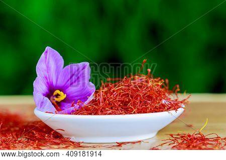 Dry Saffron Stigmas And A Single Crocus Flower In A White Plate On A Wooden Surface. Saffron .