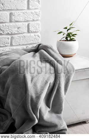 White Wooden Box With Gray Soft Fleece Blanket And Young Ficus Plant In White Flower Pot On It. Whit