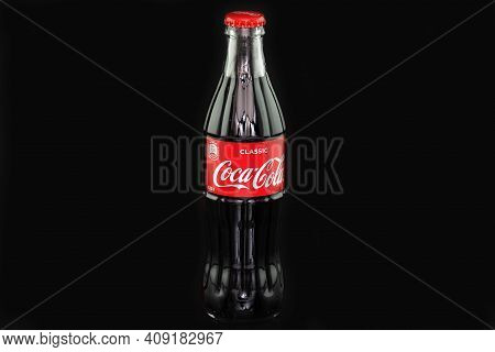 Coca Cola. A Classic Glass Bottle Of Coke With A Red Lid, Insulated On A Black Background.