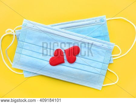 Disposable Face Masks And Two Hearts On Yellow Background . Protection, Care And Mutual Assistance C