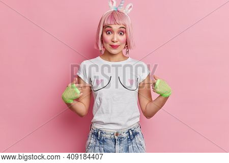 Portrait Of Asian Woman Points At Herself Wears Casual T Shirt Jeans And Sport Gloves Isolated Over