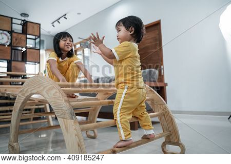 Little Baby Stands In Pikler Triangle Toys Clapping Her Hands With Sisters