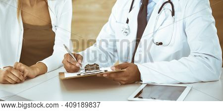 Doctor And Patient Discussing Medical Exam Results While Sitting At The Desk In Clinic, Close-up. Ma