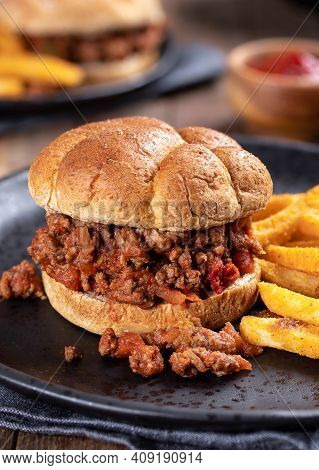 Sloppy Joe Sandwich And French Fries On A Black Plate
