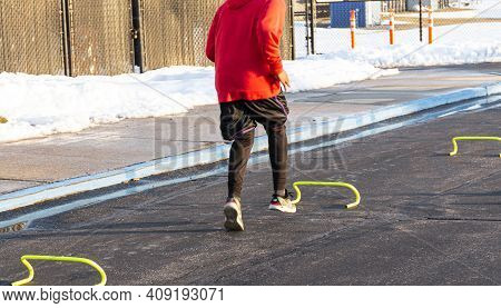 Rear View Of A  High School Track Runner Running Over Mini Yellow Hurdles In The Parking With Snow I