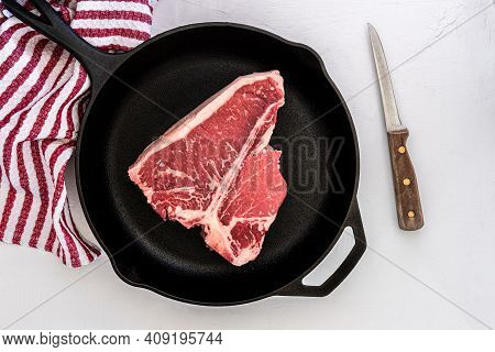 Photograph Of A T-bone Choice Cut Steak In A Cast Iron Skillet With A Boning Knife And Towel In Back