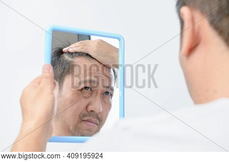 Asian Middle-aged Man Was Looking In The Mirror And Was Worried About The Many Facial Wrinkles Cause