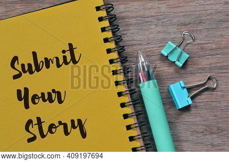 Top View Of Pen, Paper Clips And Notebook Written With Submit Your Story.