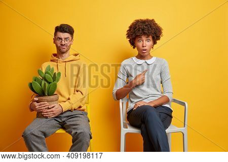 Interracial Husband And Man Try To Keep Distance Pose Separately On Chairs Move In New Apartment Iso