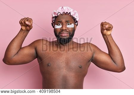 Photo Of Worried Black Man Raises Arms Clenches Fists Looks Puzzled At Camera Poses Topless Applies