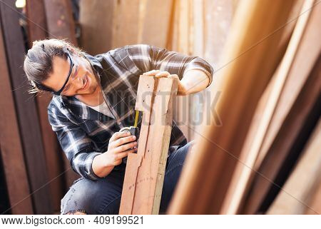 Carpenter Work In Wood Workshop Selecting Timber For His Woddwork