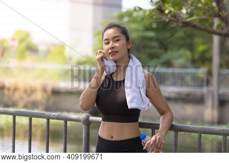 Portrait Of Woman Taking Break From Jogging, Sportswoman At Park