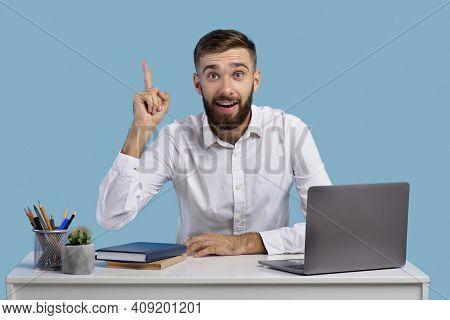 Millennial Caucasian Office Worker Having Creative Idea, Gesturing Eureka At Workplace On Blue Studi