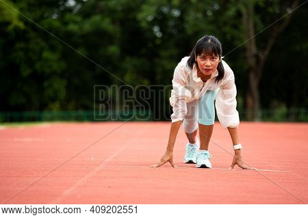 Young Asian Woman Athlete At The Start Line Of The Running Track In Stadium. Challenge Competitive T