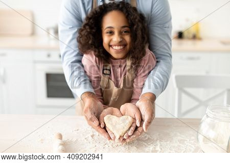 Happy Loving Family. Smiling African American Little Girl And Her Father Holding Dough In Heart Shap