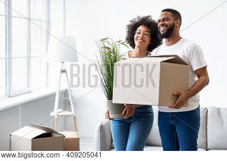 Loving Black Couple Holding Packed Boxes Moving House, Posing Standing Together In New Apartment Ind