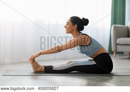 Sporty Young Woman In Sportswear Sitting On Yoga Mat, Touching Her Feet With Hands, Stretching Body