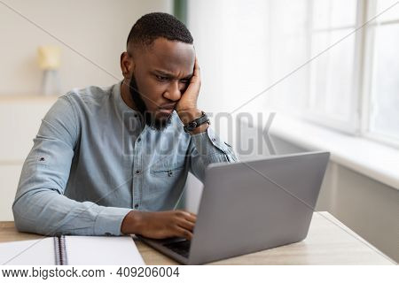 Unhappy Black Businessman Looking At Laptop Hating His Boring Job Sitting At Workplace In Modern Off