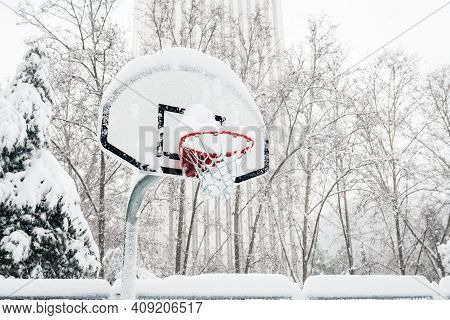 Side View Of A Street Basketball Hoop Under The Snow During The Heavy Filomena Storm In Madrid, Spai
