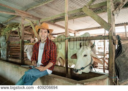 Handsome Rancher Wearing A Cowboy Hat Sitting In A Cage Holding A Digital Tablet