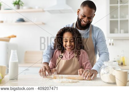 Home Bakery Concept. Happy African American Man And His Child Daughter Rolling Up Dough With Pin Tog
