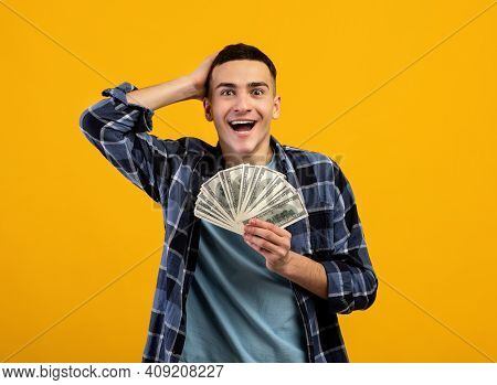 Excited Young Man Enjoying Big Jackpot, Holding Lots Of Money, Cannot Believe His Luck On Orange Stu