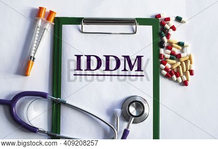 Notebook Pade With Word Iddm (insulin-dependent Diabetes) , On A Table With A Stethoscope And Pills.