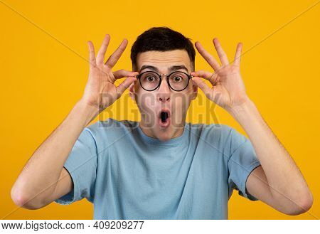 Shocked Millennial Guy Touching His Glasses, Shouting Wow Or Omg On Orange Studio Background. Handso
