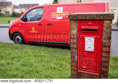 Swansea, Wales, Uk - December 12, 2020: Red Vintage Mailbox For Letters And Royal Mail Van, British