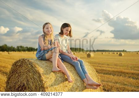 Adorable Young Sisters Having Fun In A Wheat Field On A Summer Day. Children Playing At Hay Bale Fie