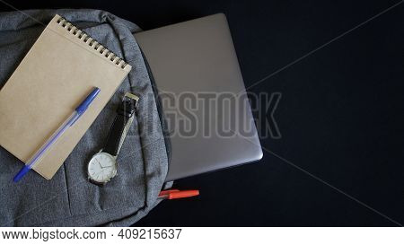A Silver Laptop Or Ultrabook, A Paper Notebook, A Wrist Watch And Two Fountain Pens Lie In A Gray Te