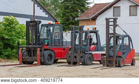 Three Used Red Forklift Tuck Vehicles Outside